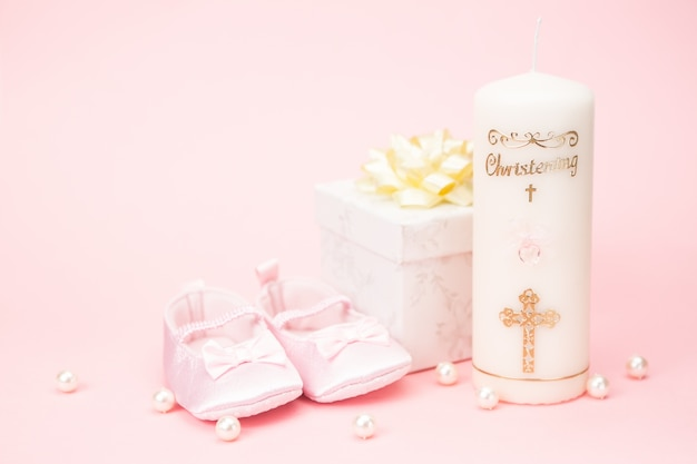 Christening candle with pink baby booties and gift box Premium Photo