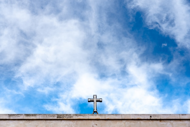 Christian cross on top of a church with a lot of blue sky copy space. Premium Photo