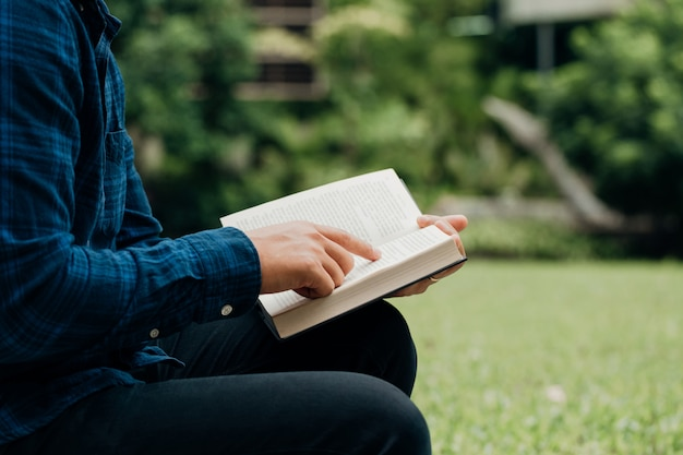 Christians and bible study concept.young man sitting reading the bible in the garden.copy space Premium Photo