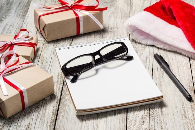 サンタキャップのメモ帳ペングラスと装飾されたギフトボックス付きのクリスマスとビジネスアイテム。 Premium写真