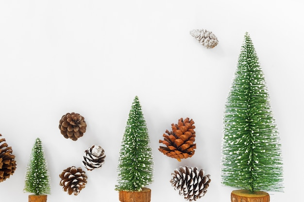 christmas and new year background christmas tree and pine cones on white paper premium