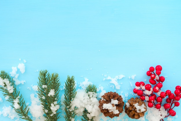 christmas and new year background fir leaves pine cones and red berry on blue