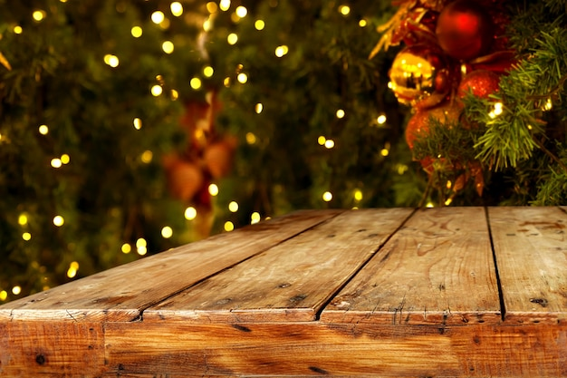 Christmas And New Year Background With Empty Dark Wooden Deck Table Over Tree Blurred