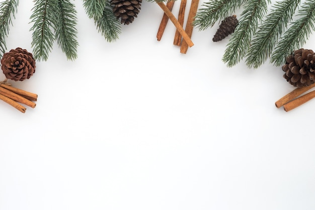christmas and new year background with fir leaves pine cones and cinnamol on white background