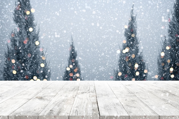 Christmas And New Year Background With Wooden Deck Table Over Tree Snow Blurred