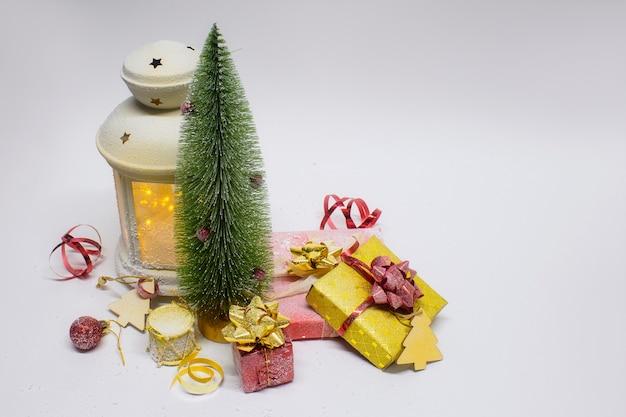 Рождественские и новогодние композиции. праздничная светящаяся лампа с елкой и украшениями, подарками и яркими бантами Premium Фотографии