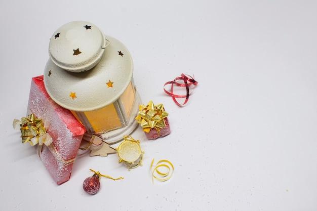 Рождественские и новогодние композиции. праздничный светящийся фонарь с украшениями, подарками и яркими бантами Premium Фотографии