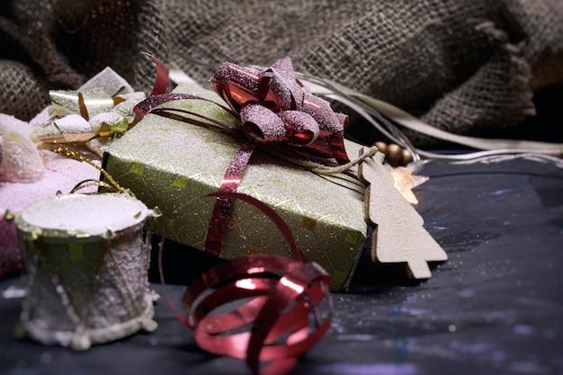 Рождество и новогоднее пространство. подарки в коробке с украшением лентами и бантами с мешковиной на темном месте. Premium Фотографии