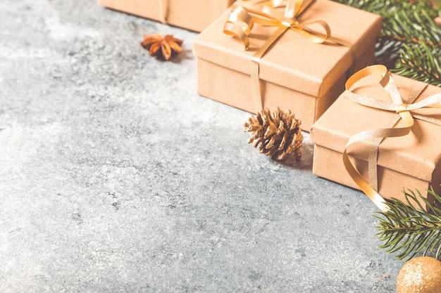クリスマスの背景。明るいコンクリートの背景にモミの枝、ギフト、お菓子、シナモンとクリスマスの構成 Premium写真