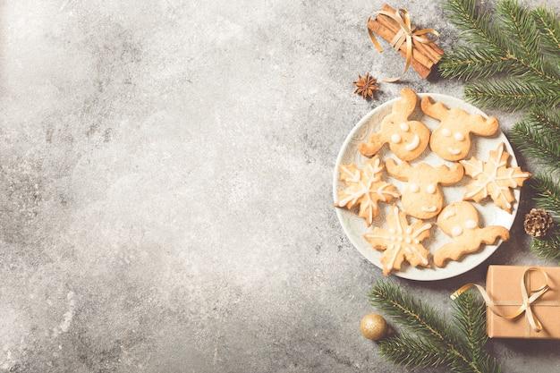 クリスマスの背景。明るいコンクリートの背景にモミの枝、ギフト、お菓子、クッキー、シナモンとクリスマスの構成 Premium写真