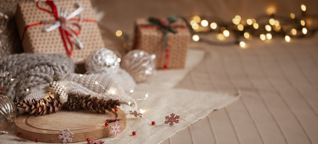 Рождественский фон композиция из сосновых шишек, гирлянд, подарочных коробок, деталей домашнего декора и размытых огней копирует пространство. Бесплатные Фотографии