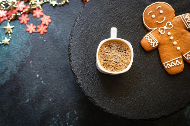 クリスマスの背景クッキージンジャーブレッドとテーブルの上のコーヒー Premium写真
