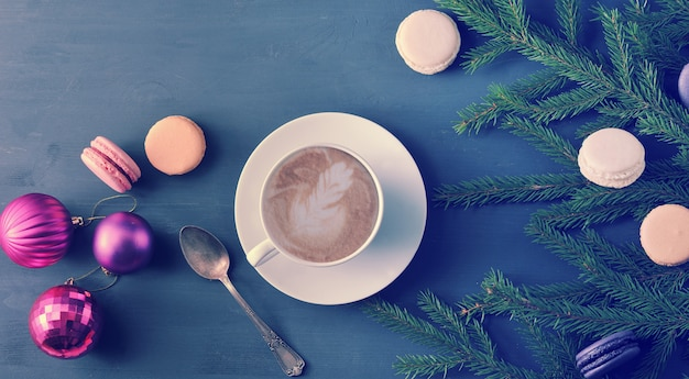 Christmas background - cup of cappuccino with cake, macarons, christmas toys and tree branches Premium Photo