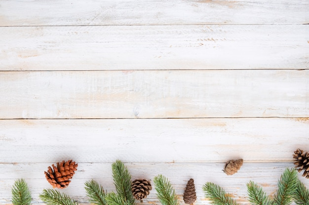 christmas background fir leaves and pine cones decorating elements rustic on white wood table - Rustic Christmas Background