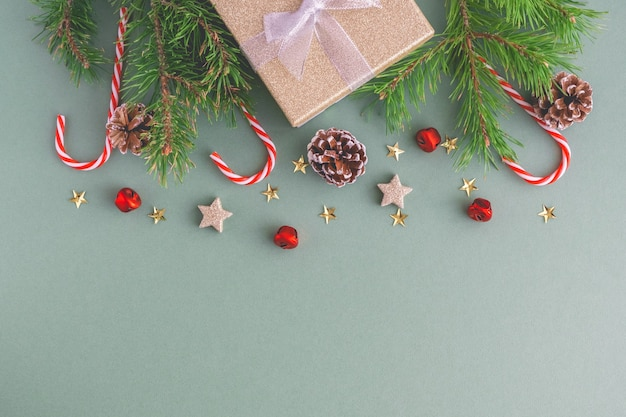 Christmas background from christmas candies, branches of a christmas tree, toys and cones with a gift box Premium Photo