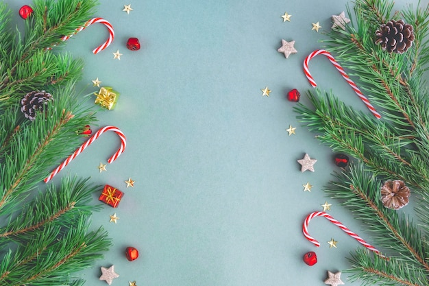 Christmas background from christmas candies, branches of a christmas tree, toys, sparkles and stars Premium Photo