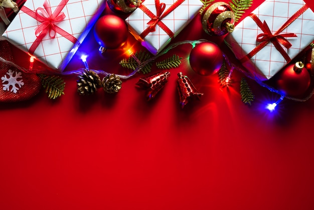 Christmas background gift box with red ball and pine cones on red background. Premium Photo