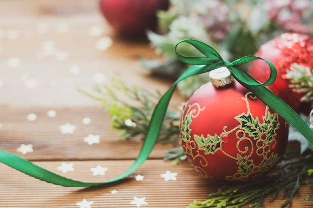 Christmas background. red beautiful bauble with green ribbon, fir branches. Premium Photo