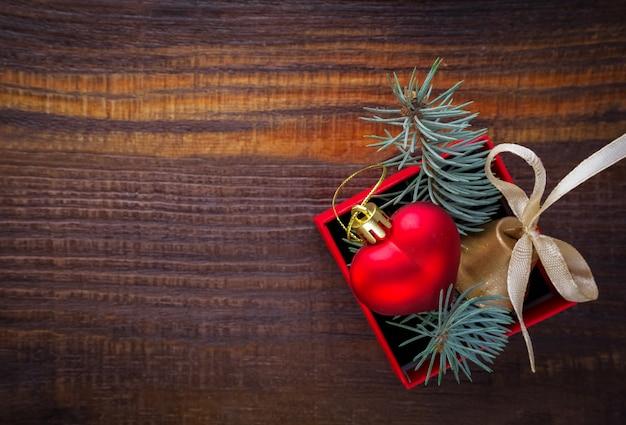 Новогодний фон: красная подарочная коробка с елочной игрушкой в форме сердца, золотой колокольчик и еловые ветки Premium Фотографии