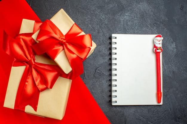 Новогодний фон с красивыми подарками с бантовой лентой на красном полотенце и блокнотом с ручкой на темном фоне Бесплатные Фотографии