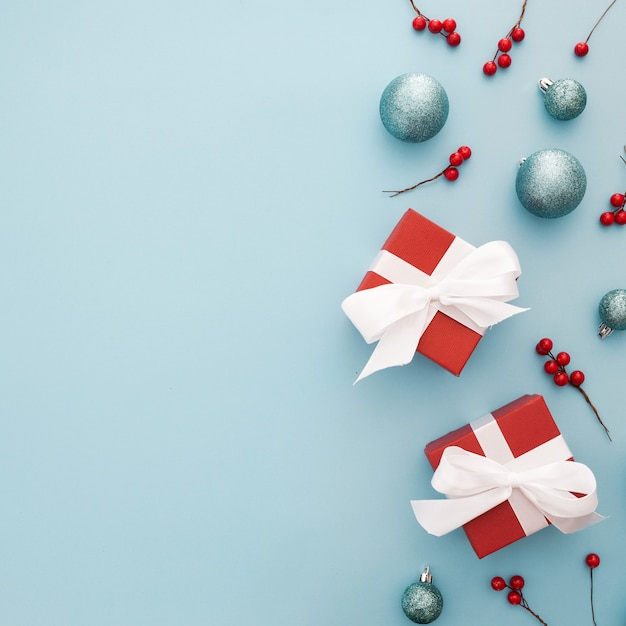 Christmas background with blue balls, red gifts and mistletoe Free Photo