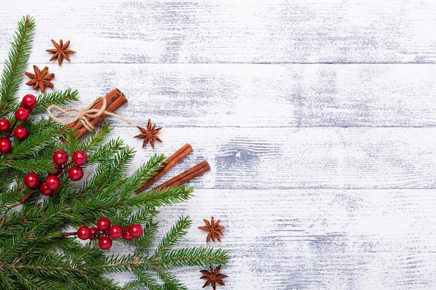 Christmas background with fir tree and cinnamon sticks on wooden table. horizontal banner Premium Photo
