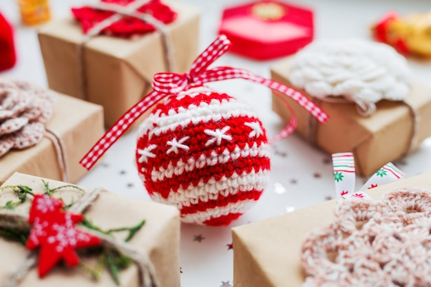 Christmas  background with presents, decorations and crocheted handmade decorative ball. Premium Photo
