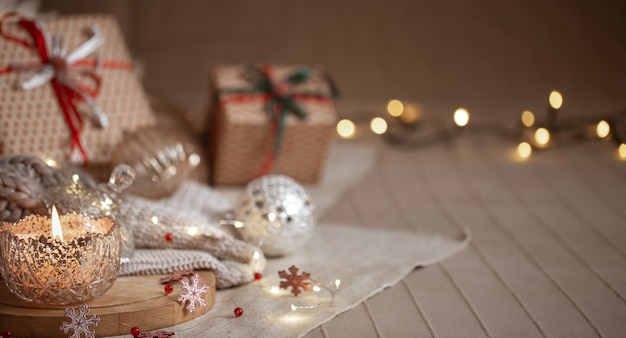 Christmas background with silver decorative burning candle, lights and gift boxes on a blurred background. copy space. Free Photo