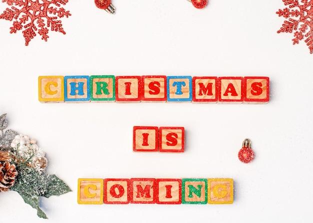 雪片、装飾、「クリスマスが来ています」の碑文とクリスマスの背景 Premium写真