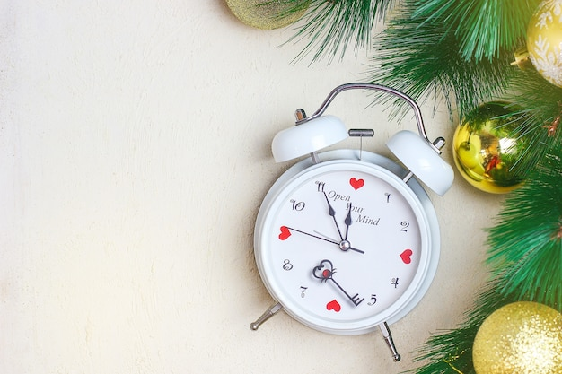 Christmas background with white red clock, golden christmas tree balls Premium Photo
