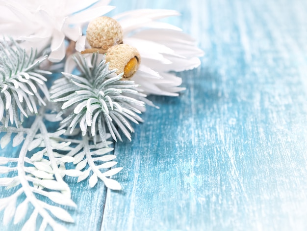 Christmas background with white spruce branches and snowflakes on a blue wooden background Premium Photo