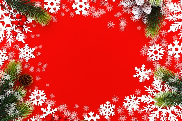 Christmas background with xmas tree branches and snowflakes on red canvas background. merry christmas card. happy new year. Premium Photo