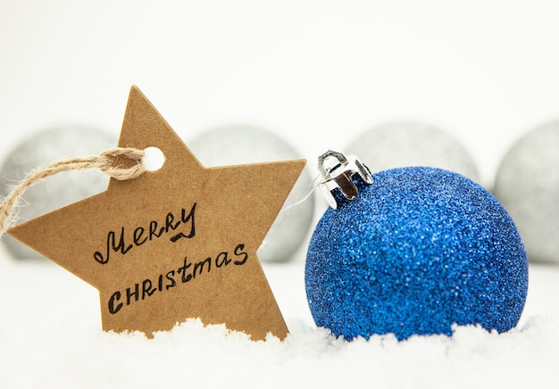 Christmas ball in blue on white snow and a star with the inscription merry christmas Premium Photo