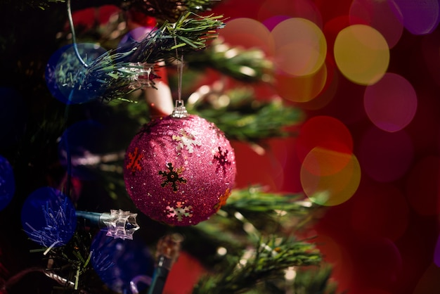 Christmas ball in tree with bokeh on red background Free Photo