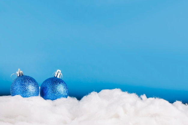 Christmas balls on decorative snow Free Photo