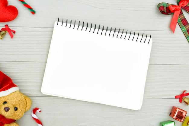 Медведь рождества и белая книга с взгляд сверху и космос экземпляра на белом деревянном столе. концепция праздника рождества. Premium Фотографии