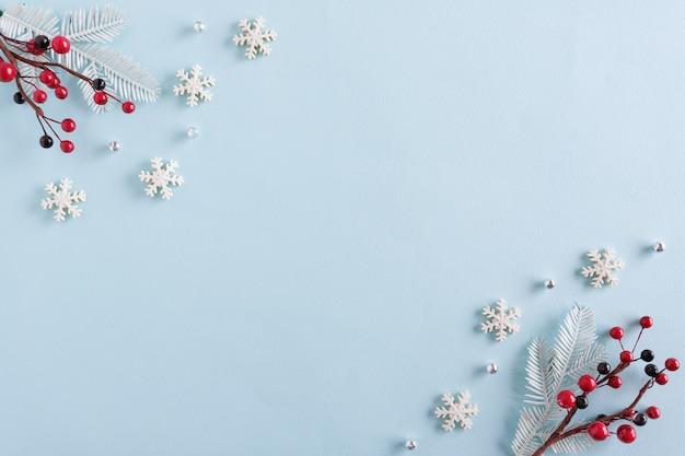 青い表面に雪片と赤い実で作られたクリスマスの境界線 Premium写真
