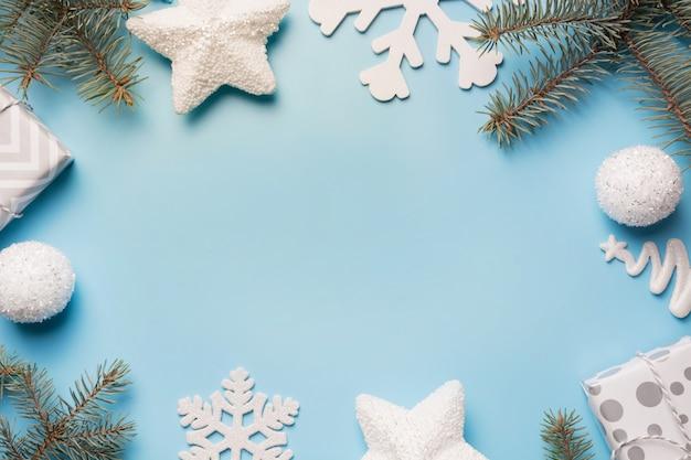 Christmas border with white decor, ball, reinderr, gift boxes on blue. Premium Photo