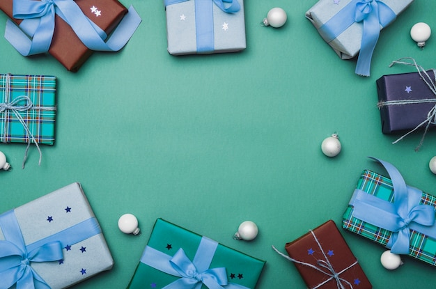 Christmas boxes with globes on green background Free Photo