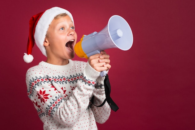 Christmas boy shouting through megaphone Free Photo