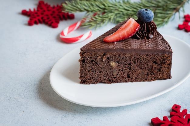 デザートのクリスマスケーキ。青い石のコンクリートテーブルの上のコーヒーとミルクのカップとチョコレートケーキのおいしい部分。朝食食品のコンセプト。お祝いの休日の装飾 Premium写真