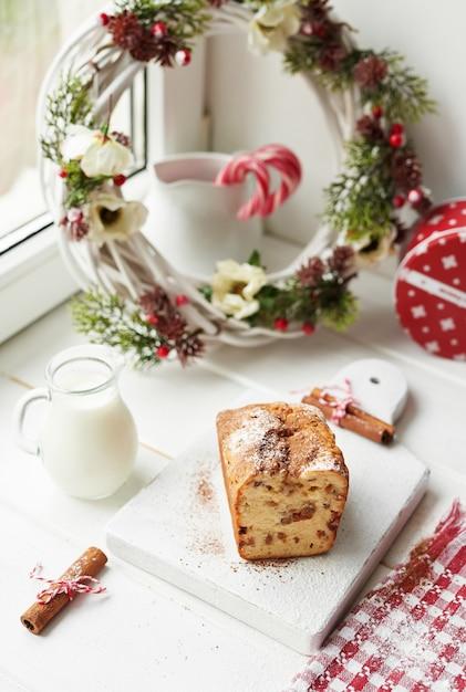 Christmas cake, milk, cocoa with marshmallows, cinnamon by the window Premium Photo