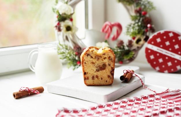 Christmas cake, milk, cocoa with marshmallows, cinnamon on plate Premium Photo