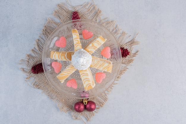 마음으로 크리스마스 케이크 조각 모양의 유리 접시에 사탕. 무료 사진