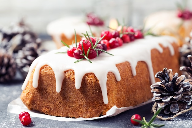 Christmas cake with sugar icing, cranberries and rosemary. Premium Photo