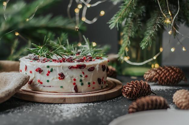 クランベリーとローズマリーで飾られた白いチーズクリームのクリスマスケーキ。 Premium写真