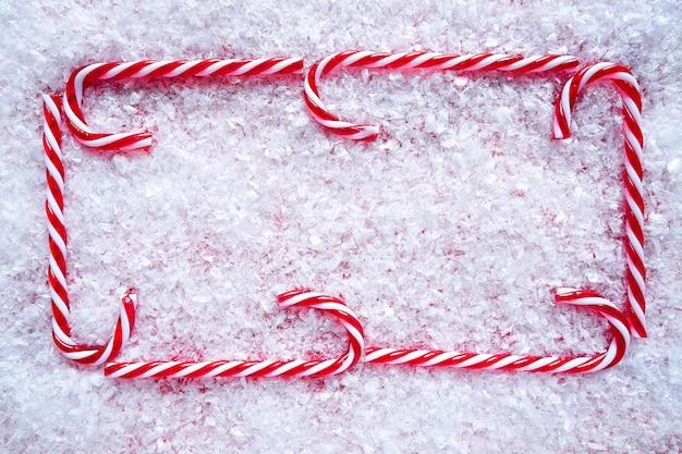 雪の上のクリスマスキャンデー杖フレーム Premium写真