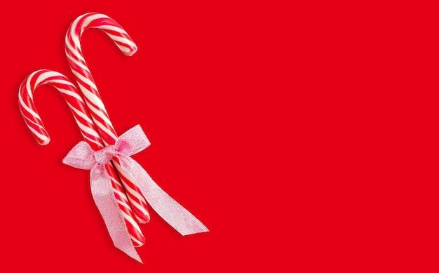 Рождественские леденцы с лентой на красном фоне с обтравочным контуром Premium Фотографии