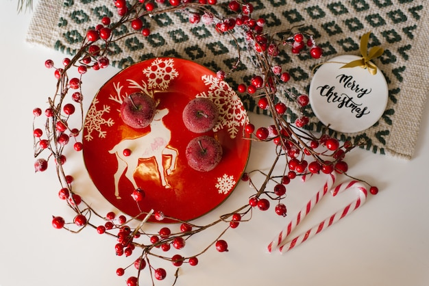 Christmas card. red plate with a deer, candied apples, cane candies and red berries on branches on the table, top view Premium Photo