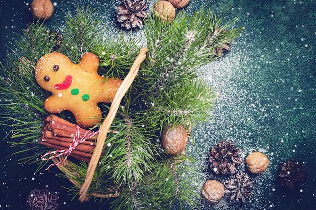 Рождественская открытка с пряничный человечек и хвойные ветви в корзине. Premium Фотографии